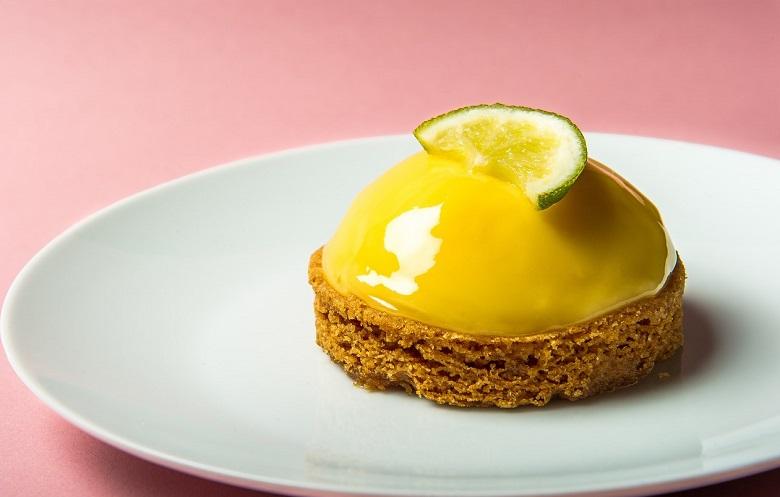 PHOTOGRAPHE CULINAIRE PROFESSIONNEL - photographie sur un fond rose d'une tarte au citron surmontée d'une tranche de citron vert et posé dans une assiette ronde blanche.
