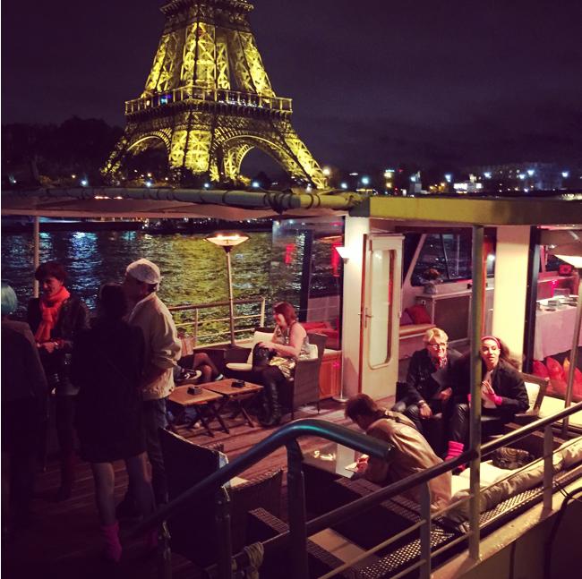 La péniche louée naviguant devant la Tour Eiffel éclairée