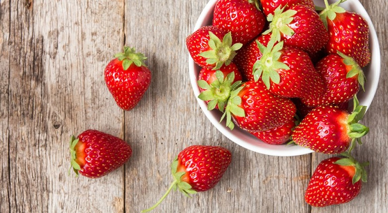 Red strawberry in a bowl on wooden background